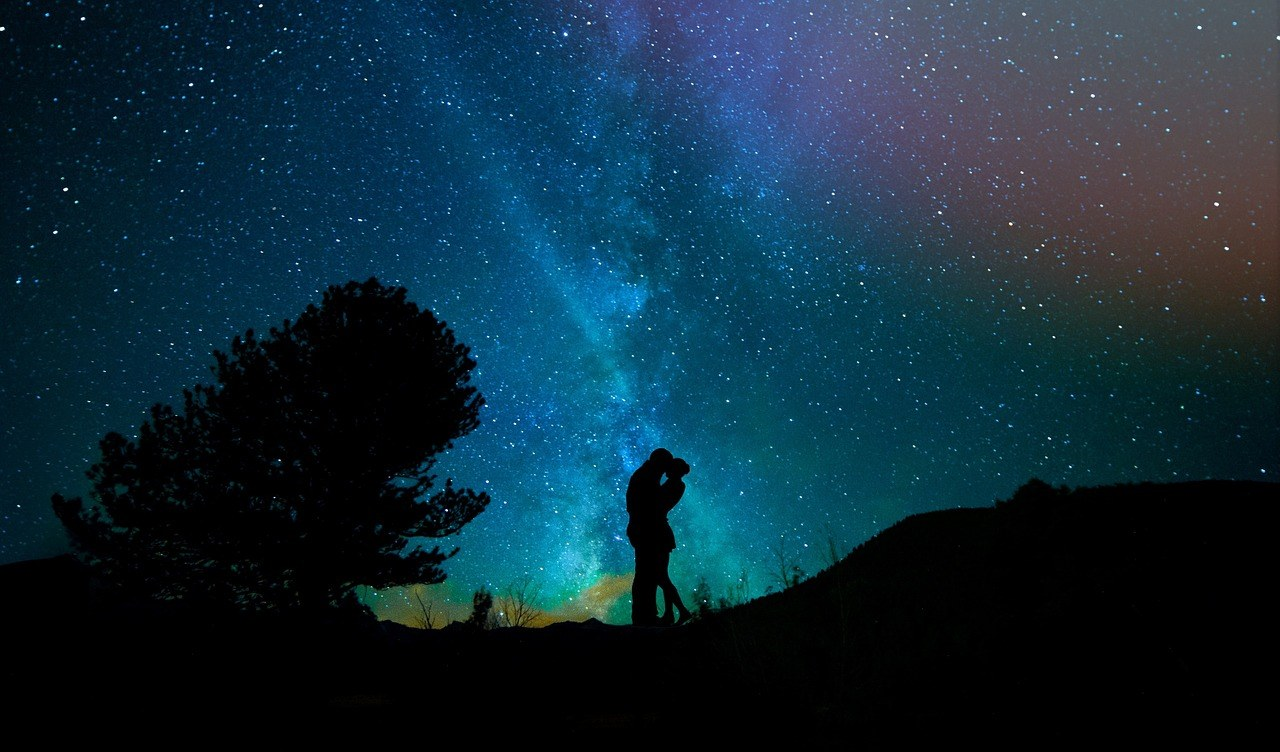 Couple kissing under night sky