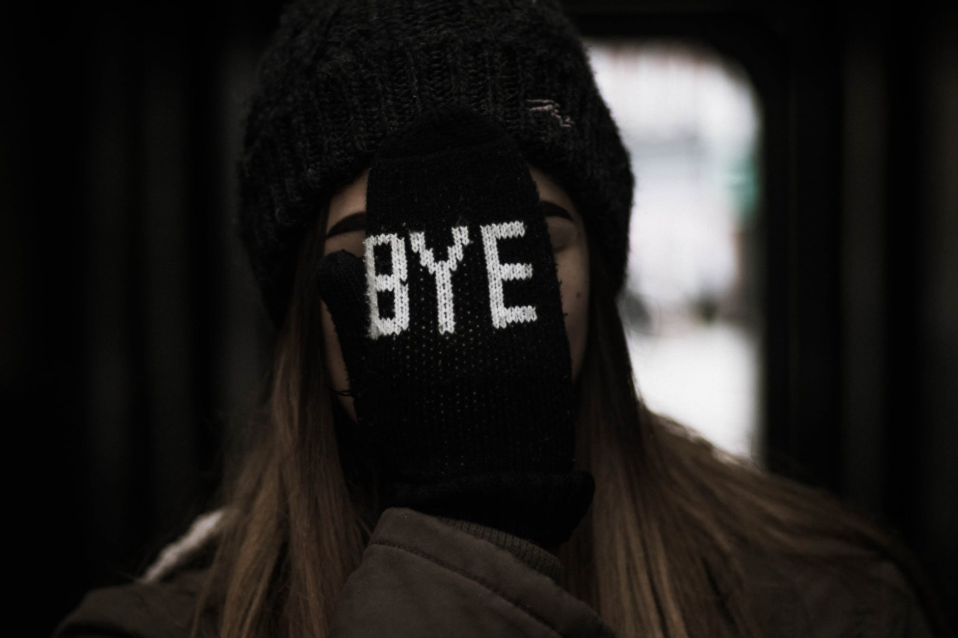 girl covering her face with glove saying bye